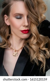Portrait of a beautiful blonde girl with red lips and evening makeup, wavy hair wearing a black velvet jacket. Healthy, clean skin. Close-up. Advertising, commercial design
