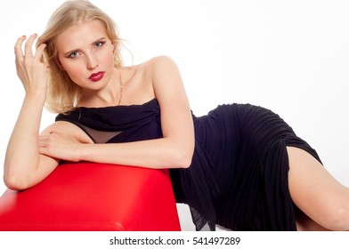 portrait of a beautiful blonde girl. She was photographed in a black dress. Photo for toning. Bright red lips.