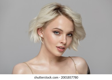Portrait of a beautiful blonde girl with a short haircut. Gray background.