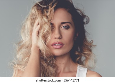 Portrait of beautiful blonde girl touching her hair and looking at camera, on gray background