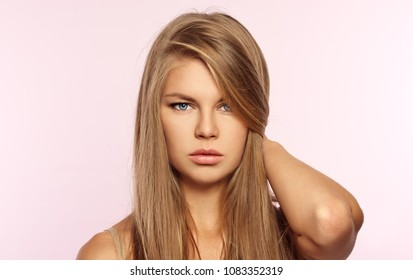 Portrait of beautiful blonde model with long straight shiny hair over pink background.
