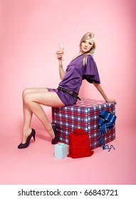 portrait of beautiful blonde party girl sitting on large birthday gift box with glass of champagne on pink