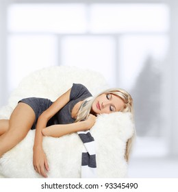 portrait of beautiful blonde sleeping on big white furry arm-chair