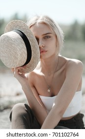 Portrait of a beautiful blonde with a straw hat close-up