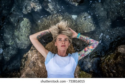 Portrait of a beautiful blonde which lies on the stone near the sea. Women's hands with a tattoo. Modern fashion girl