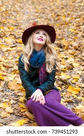 Portrait of beautiful blonde woman in autumn forest wearing fashion hat. Welcome warm autumn. Cute girl on a golden autumn background.