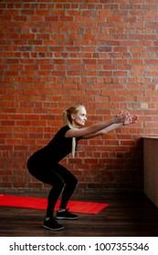 Portrait of beautiful blonde  woman in black sportswear standing against the background of a red brick wall after fitness workout.Fites concept.The girl trains, does squats