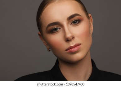 Portrait of a beautiful blonde woman in black shirt. Studio photo session. Gray background