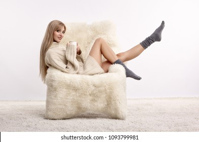 Portrait of beautiful blonde woman with cup of coffee in hands. Female is dressed in white cashmere sweater. Girl is sitting on big white furry arm-chair