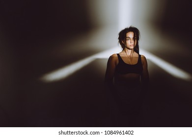 Portrait of beautiful blonde woman in darkness with soft light on her face, pensive silhuete on black background.
