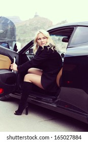 portrait of a beautiful blonde woman driving a sports car