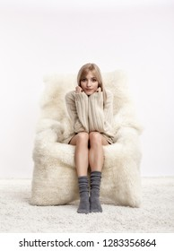 Portrait of beautiful blonde woman. Female is dressed in white cashmere sweater and woolen socks. Girl is sitting on white fur arm-chair  staying on furry carpet