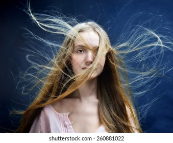 Portrait of the beautiful blonde woman with flying long hair. She is in studio .