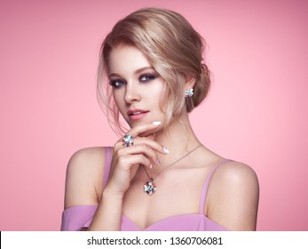 Portrait Beautiful Blonde Woman with Jewelry. Model Girl with Pearl Manicure on Nails. Elegant Hairstyle. Precious Stones and Silver. Beauty and Fashion Accessories. Perfect Make-Up. Pink Background