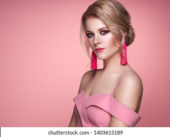 Portrait Beautiful Blonde Woman with Jewelry. Model Girl in Elegant Pink Dress. Magnificent Hairstyle. Beauty and Fashion Accessories. Perfect Make-Up. Pink Background