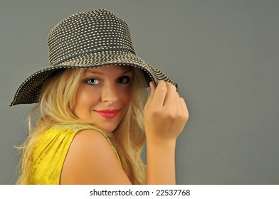 Portrait of beautiful blonde woman looking from underneath brim of spotted hat.
