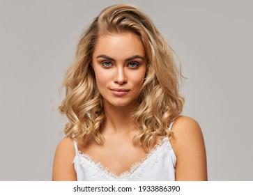 Porträt einer schönen blonden Frau auf grauem Hintergrund