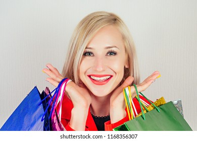 portrait of beautiful blonde woman shopaholic in a red coat with shopping bags . concept of shopaholism and sales
