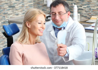 Portrait of beautiful blonde woman sitting at dentist and checking tooth whitening while male doctor holding in his hand a mirror.