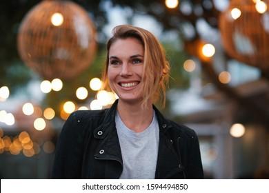 Portrait schöne blonde Frau lächeln glücklich am Stadtrundabend mit Licht auf dem Hintergrund