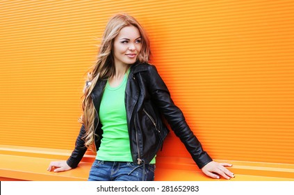 Portrait of beautiful blonde woman wearing a black rock leather jacket against the colorful orange wall, street fashion