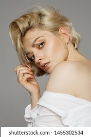 Portrait of beautiful blonde woman in white shirt and messy hair