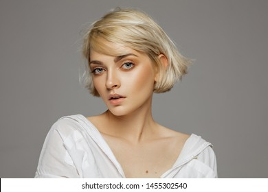 Portrait of beautiful blonde woman in white shirt and fashionable hairstyle