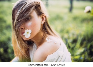 Portrait of a beautiful blonde young woman on a spring day, holding in mouth a white flower of a cherry tree.