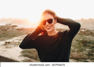 Portrait of beautiful blonde young woman in glasses on the beach with sunset light.