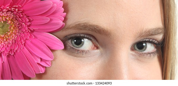 Portrait of a beautiful blue eyes of a woman with a pink flower looking at camera