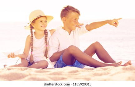 Portrait of beautiful boy and girl pointing with finger on sandy beach on bright weather