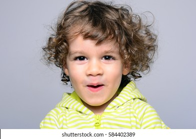Portrait of a beautiful boy with long curly hair. Toddler looking surprised and playing. Joyful adorable kid being funny