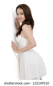 Portrait of a beautiful boy in white dress standing at the wall