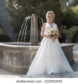 Portrait of a beautiful bride with a bouquet of flowers near the old fountain. Young fiancee in a wedding dress in the ancient park.