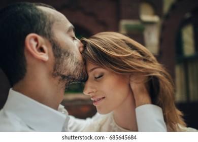 portrait of beautiful bride hugging her handsome groom outdoors