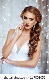 Portrait of Beautiful Bride in Lights. Fashion Dress and MakeUp. Beautiful White Bokeh