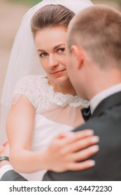 Portrait of beautiful bride looking at camera from behind the groom