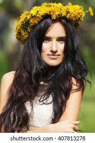 Portrait of a beautiful bride. Perfect brunette hair and blue eyes. A wreath of dandelions on the head of model. White dress. Summer shot.