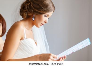 Portrait of a beautiful bride reads wedding ceremony program