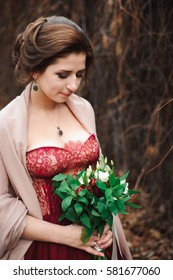 portrait of a beautiful bride in a red dress with a wedding bouquet in a hand