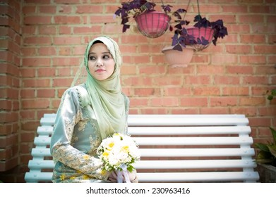 Portrait of beautiful bride sitting in front of brick wall background.