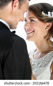 portrait of beautiful bride smiling and staring into her handsome groom