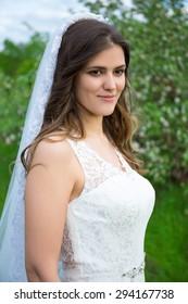 portrait of beautiful bride walking in summer garden