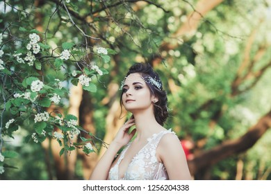 portrait of a beautiful bride in a wedding dress near a flower tree