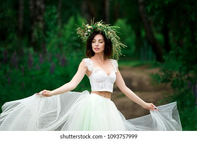 Portrait of a beautiful bride in a white dress and a wreath