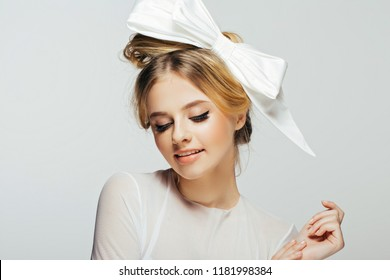 portrait of a beautiful bride in a white dress, hairstyle with a huge bow on her head.Art modern style. Blue eyes. Professional make up