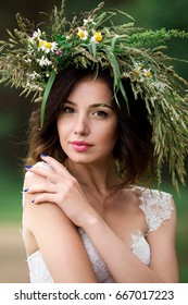 Portrait of a beautiful bride in a white dress and a wreath of Forest flowers
