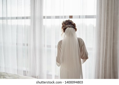 Portrait of beautiful bride in white silk dressing gown with curly hairstyle and veil standing near window in bedroom, copy space. Bride's morning preparation. Back view
