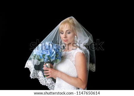 95a5d127806 Portrait of a beautiful bride in white veil with wedding blue flowers in  the studio on