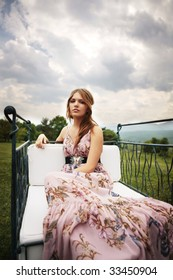 a portrait of a beautiful bridesmaid in a pink dress smiling in the middle of the nature seating and looking at the camera